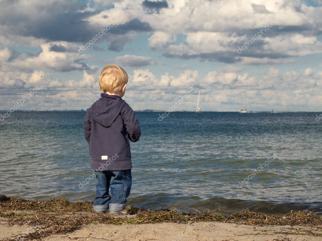 Little boy at a beach looking towards the sea in autumn ...