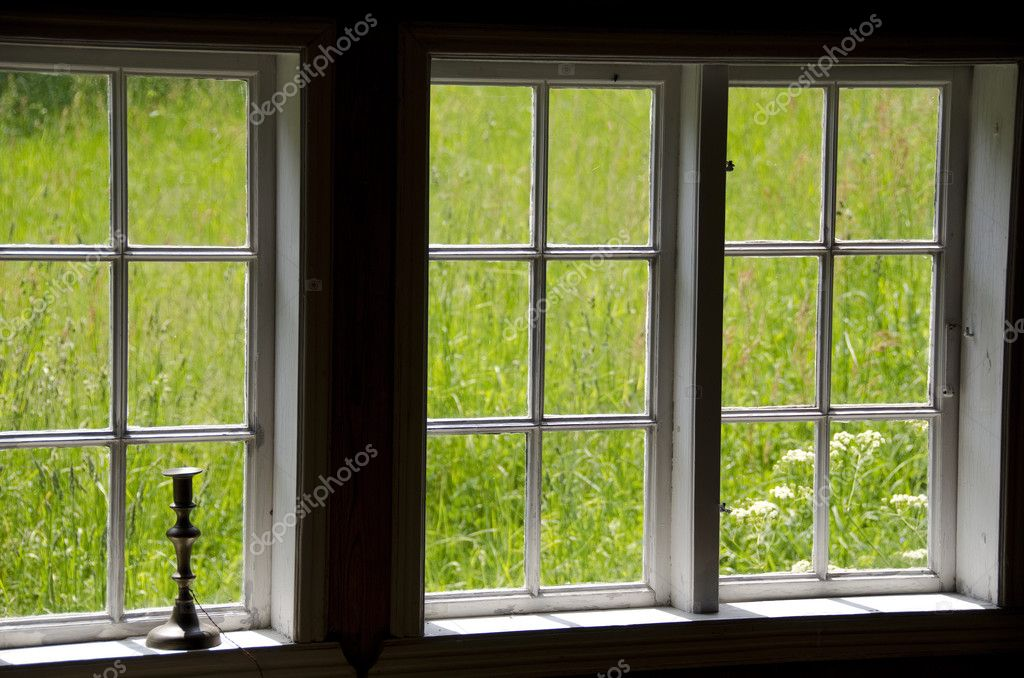 View on a meadow out of old windows with a candle stick — Stock Photo #6363875