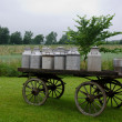 Old milk cans on waggon - Stock Photo