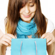 Surprised girl with blue shopping bag — Stock Photo