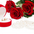 Bouquet of red roses and jewellery — Stock Photo