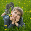 Boy lying on dandelion meadow — Stock Photo