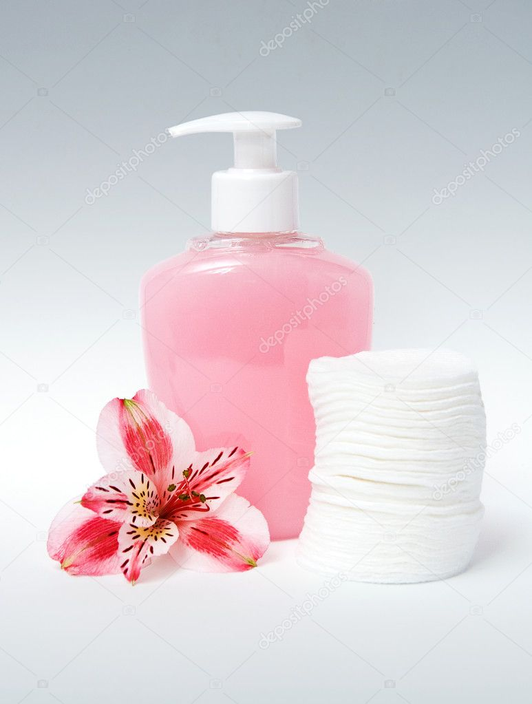 Pink bodycare item with cotton pads and flower on blue background  Stock Photo #5966510