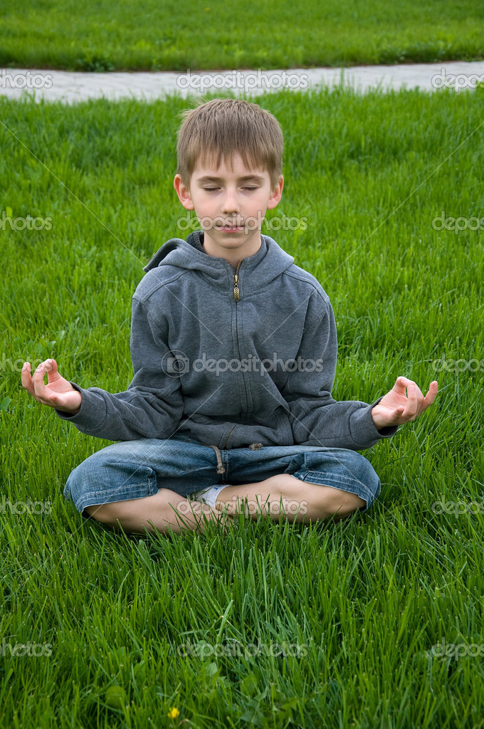 Eight years old boy practices yoga outdoors — Stock Photo #5966738
