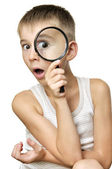 Surprised boy with magnifying glass — Stock Photo