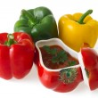 Red, green and yellow bell peppers with red ceramic ornament — Stockfoto