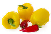 Three fresh yellow bell pepper and glass chilli peppers isolated on white — Stock Photo