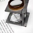 Macro of text and loupe on printed sheet — Stock Photo #5985580