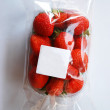 Strawberries in plastic box with white label — Foto Stock