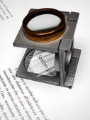 Macro of text and loupe on printed sheet — Stock Photo