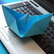 Foto Stock: Paper boat sailing on laptop