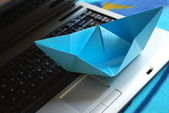 Paper boat sailing on laptop — Stock Photo