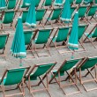 Green deckchairs and umbrellas on the beach - Stock Photo