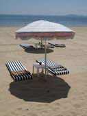Umbrella and beds on the beach — Stock Photo