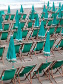 Green deckchairs and umbrellas on the beach — Photo