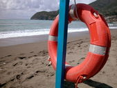 Red lifebelt on the beach — Stock Photo
