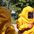 Man iin yellow chemical suit - Stock Photo