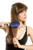 Woman combing her long hair with hairbrush — Stock Photo