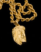 Gold pendant in shape the face of Christ — Stock Photo