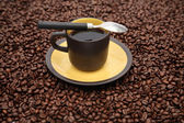 Coffeecup and spoon on the beans — Stock Photo