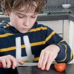 Boy cutting tomato — Stock Photo
