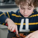 Boy cutting tomato — Stock Photo #5917842