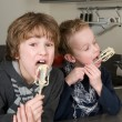 Stock Photo: Boys Eating Dough From Beater