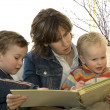 Mother and two son's reading a book — Stock Photo