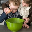 Stock Photo: Boy and mother making the dough for the cakes