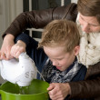 Stock Photo: Mother and son mixing the dough