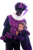 Zwarte Piet with child — Stock Photo