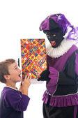 Zwarte Piet gibt ein Kind seine Gegenwart — Stockfoto
