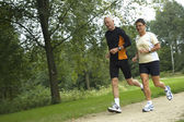 Senior par corriendo en el bosque — Foto de Stock