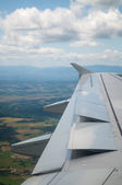 Wing of airplane going to land — Стоковое фото
