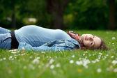 Těhotná žena relaxační v parku — Stock fotografie