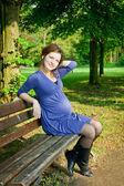 красивая беременная женщина, отдыхая в парке — Стоковое фото