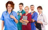 Young smiley female doctor and her team — Stock Photo