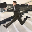 Businessman running on stair - Stock Photo