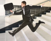 Businessman running on stair — Stock Photo