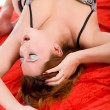 Young sensual woman on red fabric — Stock Photo