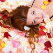 Young sensual woman lying on petal — Stock Photo