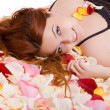 Young smiling woman  lying on petal - Stock Photo
