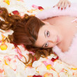 Young woman lying on petals — Stock Photo