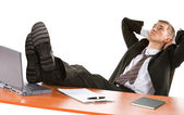 Depressed businessman with legs on table — Stock Photo