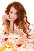 Young sensual woman lying on petals — Stock Photo