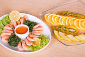 Shrimps and fruits on table — Stock Photo