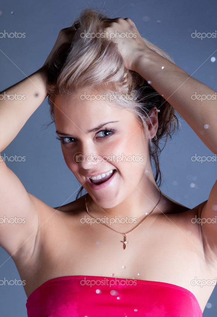 Young smiley blonde woman with falling water droplets at black background  Foto de Stock   #6706567
