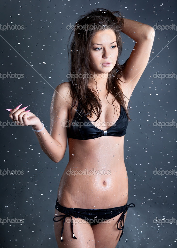 Young woman with water droplets falling at black bacground — Stock Photo #6706572