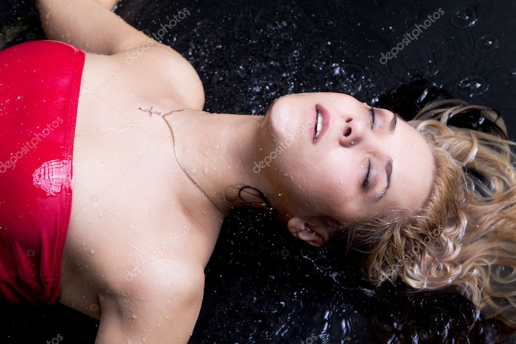 Young expressive blonde woman lying in water with  splashes and droplets — Stock Photo #6706621