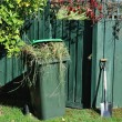 Stock Photo: Green bin and spade in backyard